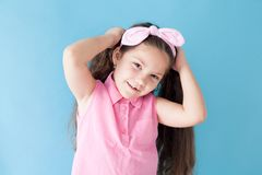 Small beautiful girl with bow and pigtails royalty free stock photography