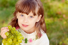 Small beautiful girl eats green grapes Stock Image