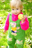 Small beautiful girl on green herb by autumn. Small beautiful girl in green suit on green glade with apple Royalty Free Stock Photos