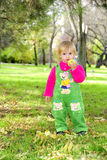 Small beautiful girl on green herb by autumn. Small beautiful girl in green suit on green glade with apple Stock Photo