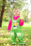 Small beautiful girl on green herb by autumn Royalty Free Stock Photography