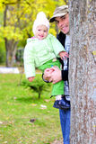 Small beautiful girl in green suit with father Stock Photography