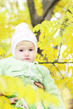 Small beautiful girl in green suit under yellow sheet Stock Photos