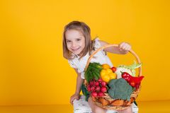 Small beautiful girl holding a basket of fresh fruit and vegetables healthy food stock photos