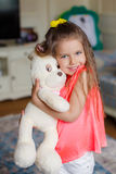 A small beautiful girl hugs funny bear Stock Photo