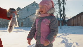 Small, beautiful girl laughing standing in the snow. stock footage