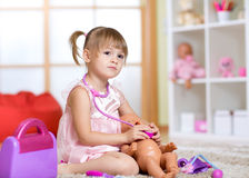 Small beautiful girl listens by means of Stock Photos