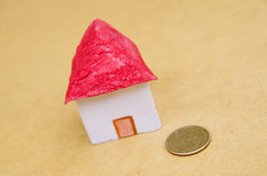 Small beautiful house with a coin in front of the housing model pretending: house prices, house buying, real estate Royalty Free Stock Images