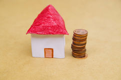 Small beautiful house with coins stacked in front of the housing model pretending: house prices, house buying, real Royalty Free Stock Image