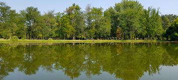 Small beautiful panorama lake with reflection of nearby green big trees. royalty free stock photography