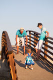 Small beautiful pretty girl is walking on wooden bridge to his father. Little beautiful pretty girl is walking on wooden bridge to his father Royalty Free Stock Photography