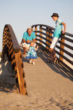 Small beautiful pretty girl is walking on wooden bridge to his father. Royalty Free Stock Image
