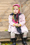 The small beautiful serious girl sits in a scarf. At a fence Stock Photo