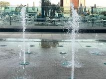 A small beautiful singing fountain in the open air, on the street. Drops of water, jets of water frozen in the air in flight again. St the backdrop of an open stock photography