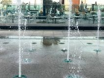 A small beautiful singing fountain in the open air, on the street. Drops of water, jets of water frozen in the air in flight again. St the backdrop of an open royalty free stock photo
