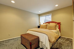 Small bedroom interior with bed and wicker ottoman stock images