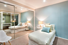 Small bedroom with pillows on the a single bed and lights turned Royalty Free Stock Photography