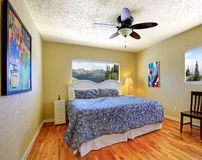 Small bedroom with yellow walls, mountain view and grey bed. Stock Photos
