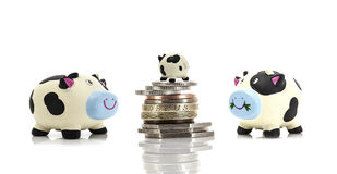 Small Beginnings - Small  Piggy Bank on top of coins with two la Royalty Free Stock Photos