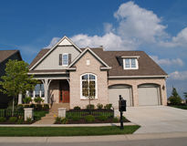 Small Beige Brick Home with Two Car Garage in Fron stock image