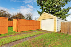 Small beige detached garage at the fenced backyard Stock Images