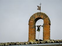 Small bell, cross and old weather vane on a roof. Brick half-point arch with small bell, cross and old weather vane on a roof stock photography