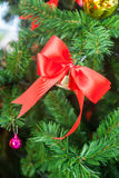 Small bell with red ribbon ornament on Christmas Tree Royalty Free Stock Images