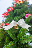 Small bell with white ribbon ornament on Christmas Tree Stock Photos