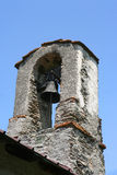 Small belltower of an old mountain church made of stones Stock Photo