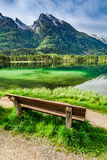 Small bench at the Hintersee lake at sunrise Royalty Free Stock Photo