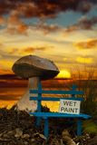 Small bench with wet paint at sunset. Small bench with wet paint and giant mushroom at sunset Stock Images
