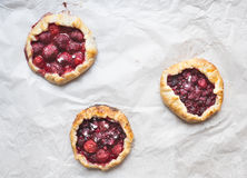 Small berry galettes on white paper. Background Royalty Free Stock Images