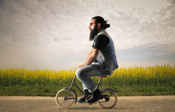 Small bicycle. Man on top of small bicycle walking in the countryside Royalty Free Stock Photo
