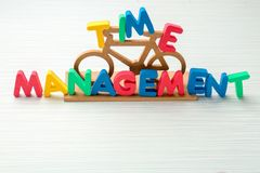 Small bicycle and phrase \'Time management\' composed from letters on table royalty free stock photos