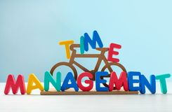 Small bicycle and phrase \'Time management\' composed from letters on table royalty free stock photography