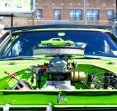 Small and Big. Lime green mini copy of an antique car placed on top of the engine, during the Maspeth 2012 Annual Antique Car Show Royalty Free Stock Images