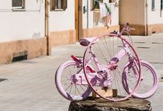 Small bike painted in pink in Alghero Royalty Free Stock Photo