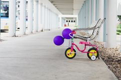 Small bike with beautiful color balloons. And behind The long wa. Small bike parked safely. Concept of family warmth between mother and daughter Royalty Free Stock Photo