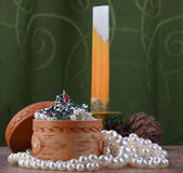 Small birch bark casket surrounded by pearls on background of candle Royalty Free Stock Photos