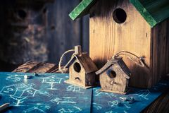 Small bird feeder in wooden workshop and construction plan. Closeup of small bird feeder in wooden workshop and construction plan stock image