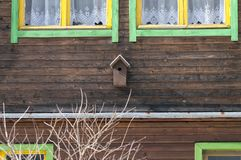 A small bird house on the facade. Of wooden country style house, outdoor cropped image stock photo