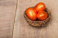 Small bird's nest with orange foil eggs Stock Images
