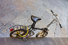 Small black bicycle parked on a street Stock Photo