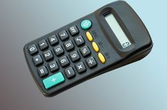 Black calculator on a blue background royalty free stock photo