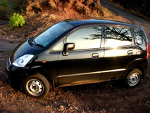 Small Black Car. A small black car parked on a road on a hill Royalty Free Stock Photo