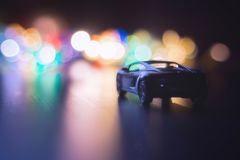 The lights of the big city . night traffic . car on night road . night trip around the city. Small black car in dark night on the road and night multi-colored Royalty Free Stock Photography