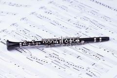 Small black clarinet on notes Royalty Free Stock Photos