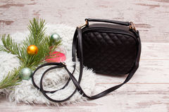 Small black female handbag on a wooden background, fir branch with ornaments, candle. fashion concept Royalty Free Stock Photos