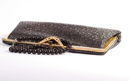 A small black handbag and black beads. A small black handbag with shiny buckle and round black beads Stock Photography