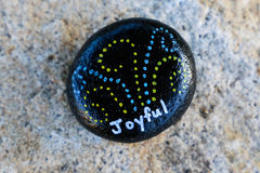Small black painted rock with the word Joyful in white letters. Small black painted rock with a message painted in white letters stating `Joyful.`  Stone is Royalty Free Stock Photos